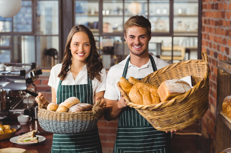 Smiling co-workers holding breads basket stock photo