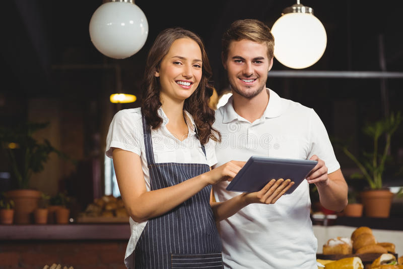 Smiling co-workers holding a tablet. Portrait of co-workers holding a tablet at the coffee shop stock photos