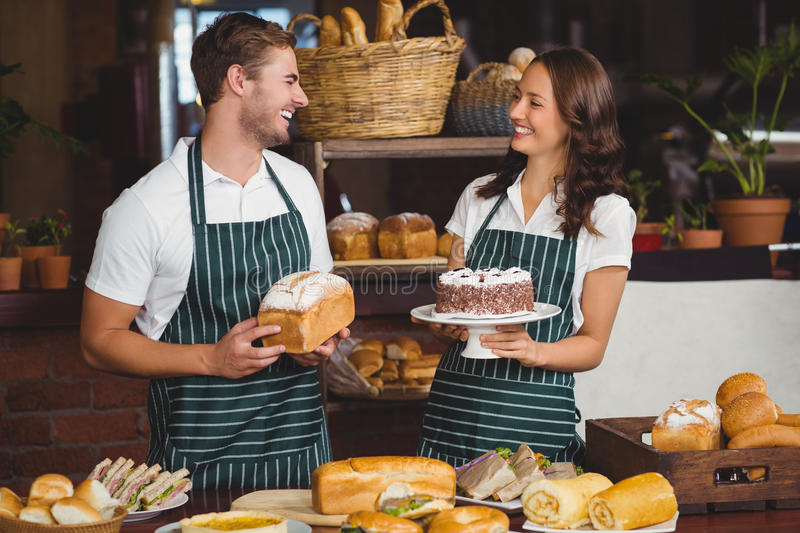 Smiling co-workers showing bread and cake. At the coffee shop stock images