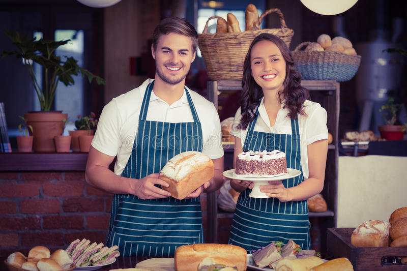 Smiling co-workers showing bread and cake. At the coffee shop stock photo