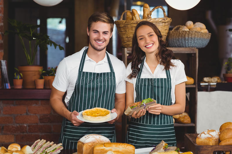 Smiling co-workers showing sandwich and pie. At the coffee shop royalty free stock images