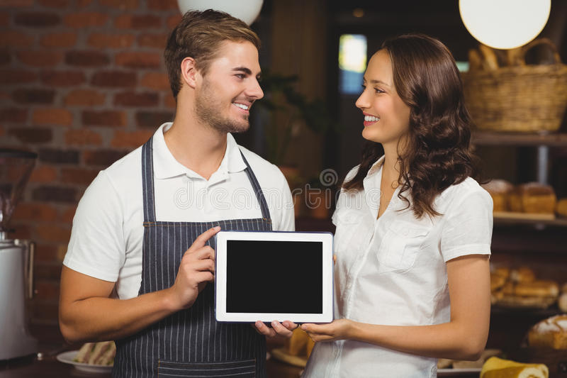 Smiling co-workers showing a tablet. At the coffee shop royalty free stock photos