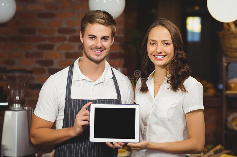 Smiling co-workers showing a tablet. Portrait of co-workers showing a tablet at the coffee shop royalty free stock photo