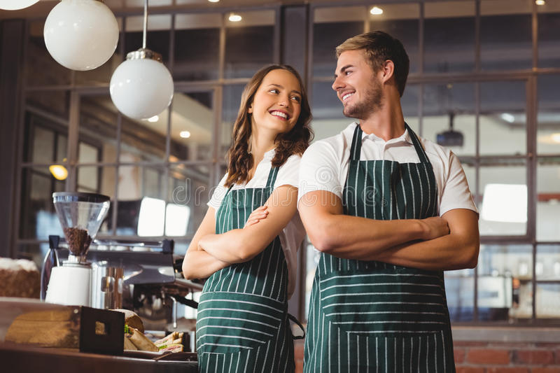 Smiling co-workers standing together. Co-workers standing together with arms crossed at the coffee shop royalty free stock photography