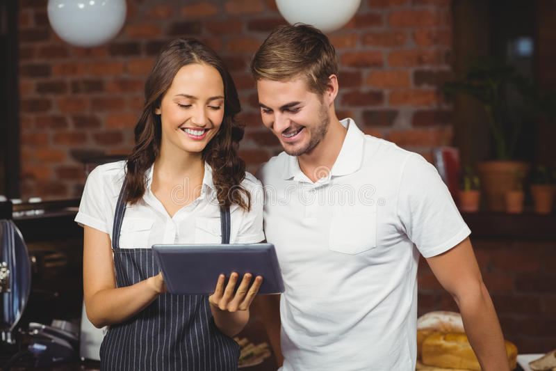 Smiling co-workers using a tablet. At the coffee shop stock images
