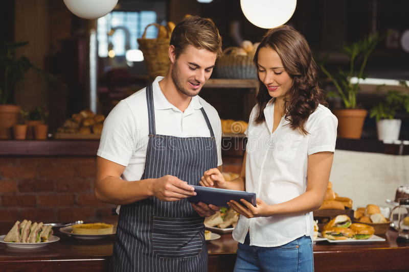 Smiling co-workers using a tablet. At the coffee shop royalty free stock photography