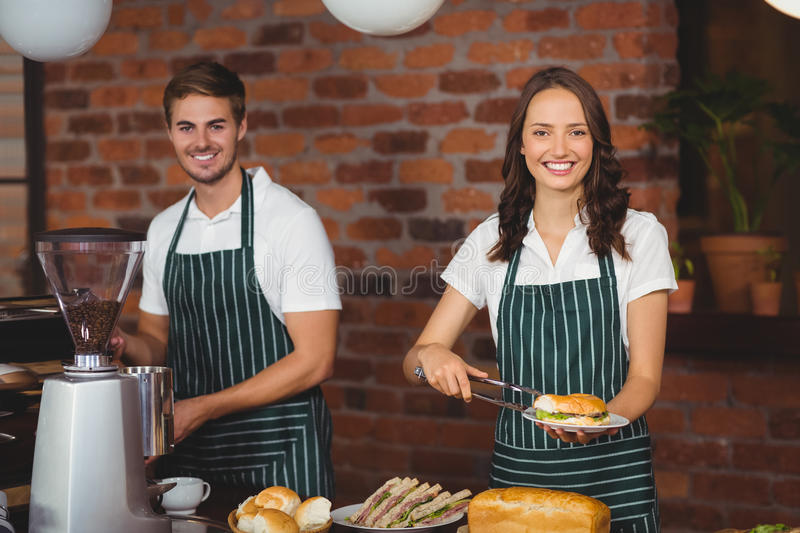 Smiling co-workers working together. Portrait of co-workers working together at the coffee shop royalty free stock photos