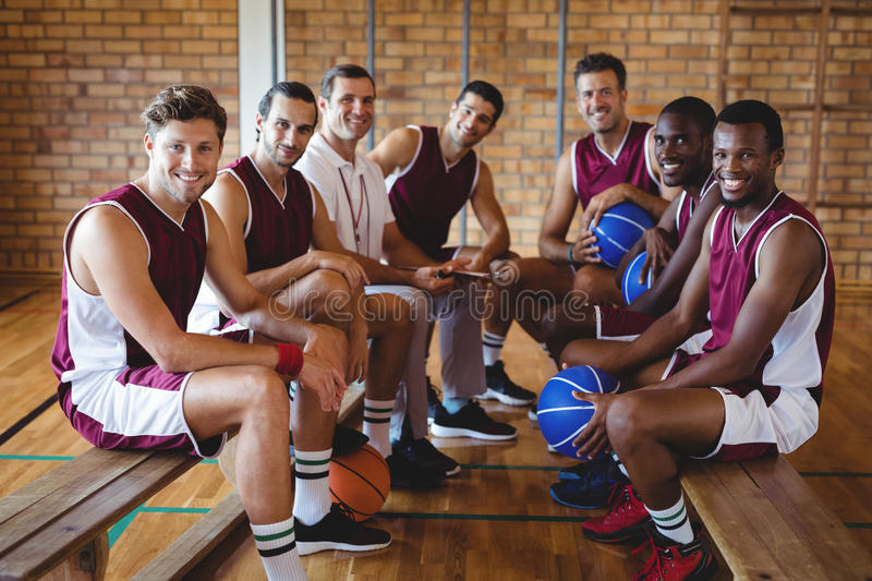 Smiling coach and basketball player sitting on bench. Portrait of smiling coach and basketball player sitting on bench in the court stock photography