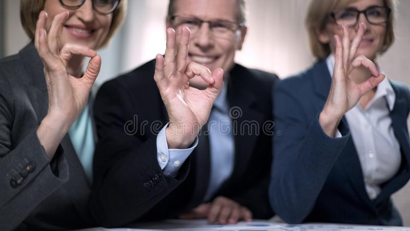 Smiling colleagues promise excellent service, professionals showing ok sign. Stock photo royalty free stock image