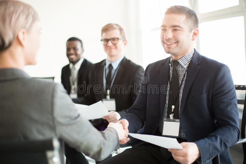 Smiling colleagues shaking hands on meeting royalty free stock photography