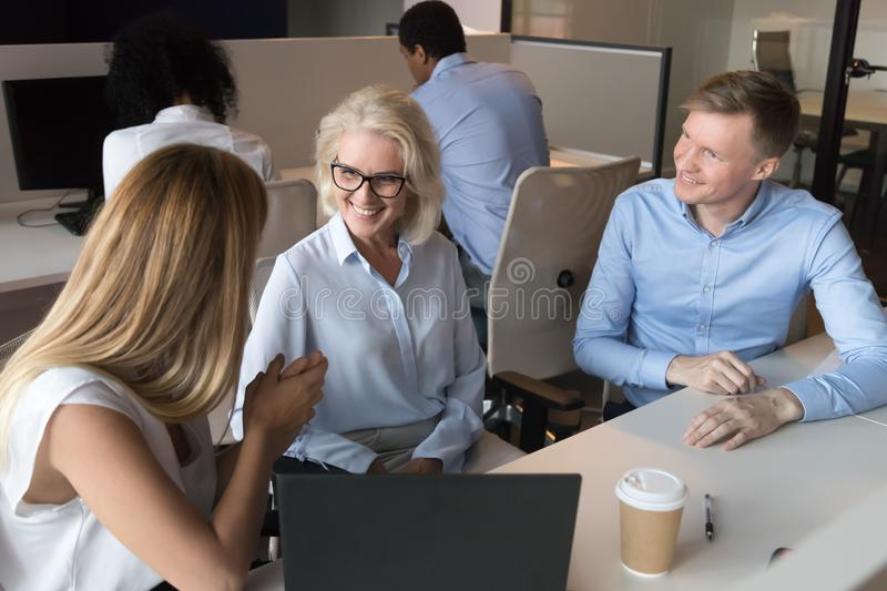 Smiling colleagues talk sharing thoughts at workplace stock photos