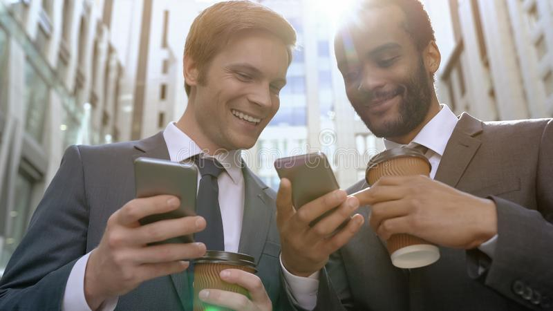 Smiling colleagues using easy mobile app on smartphone, coworkers on lunch break royalty free stock photo