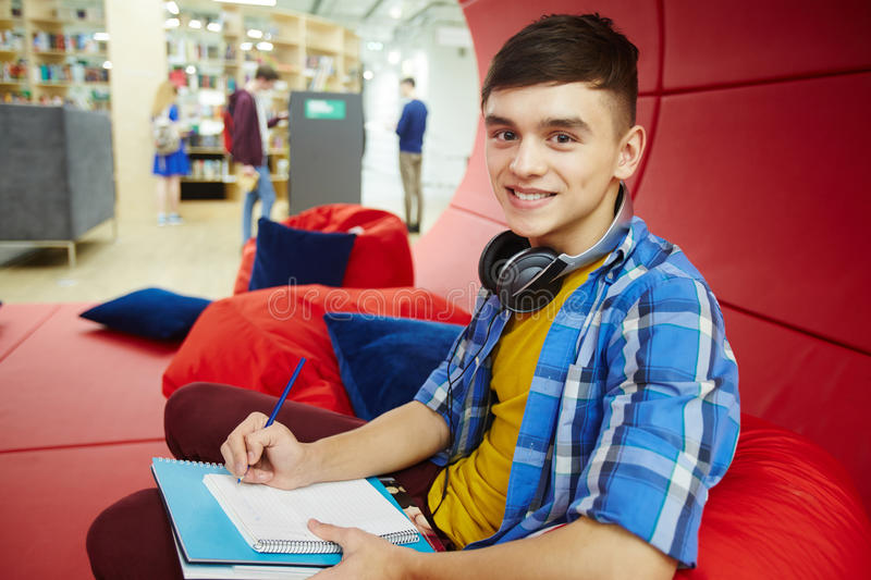 Smiling College Student in Modern Workspace. Portrait of smiling student resting on bean bag in creative workspace of modern college, studying and looking at royalty free stock photo