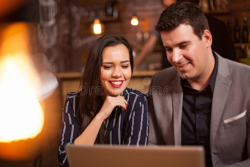 Smiling collegues sitting together in a coffee shop working on a project. Coworkers cocentrating. Good commnication stock photography