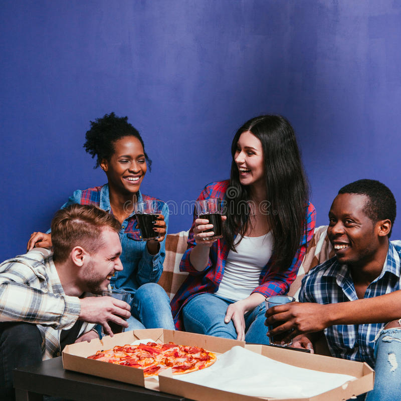 Smiling company have fun at home, hot pizza party. Company Fun Home Pizza Party Leisure Smile Laugh Interracial Friend Group Friendship Background Concept stock photos