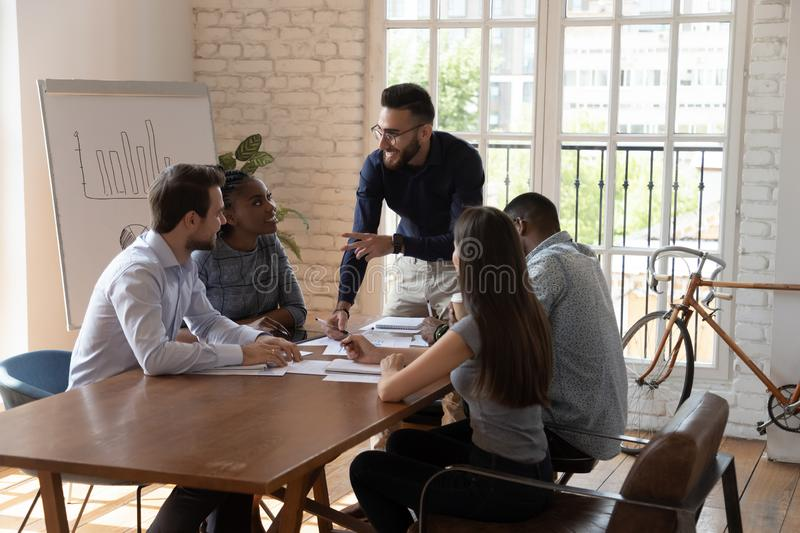 Smiling confident arabic team leader pointing at coworkers. stock photo
