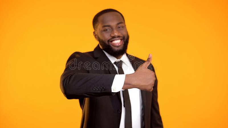 Smiling confident black businessman making thumbs-up gesture, excellent service stock photos