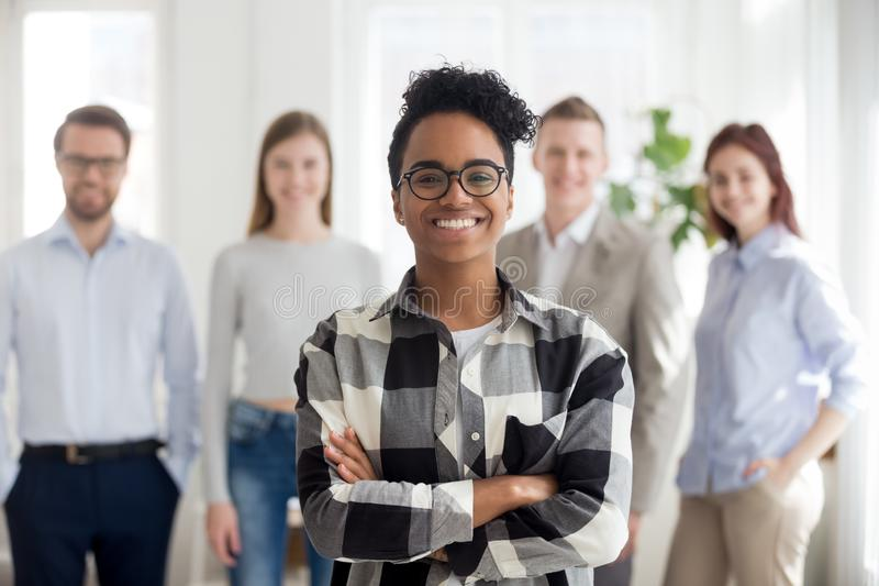 Smiling confident black company employee standing with colleagues at background stock image