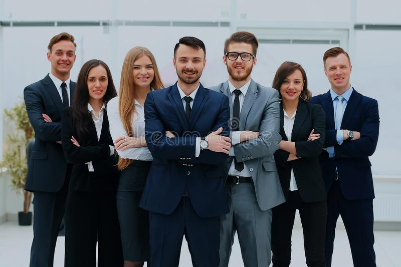 Smiling and confident business team standing in front of a bright window. royalty free stock image