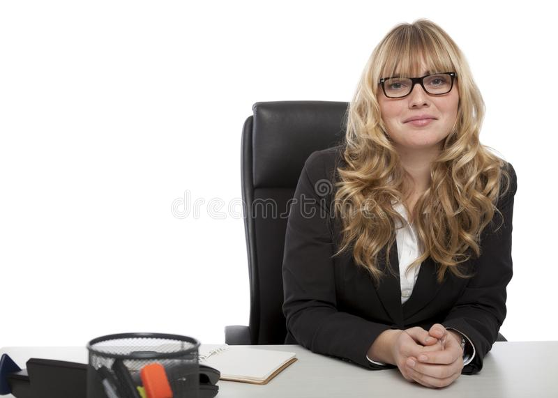 Smiling confident businesswoman in glasses. Smiling confident attractive young businesswoman in glasses sitting relaxing at her desk looking at the camera with a royalty free stock photo