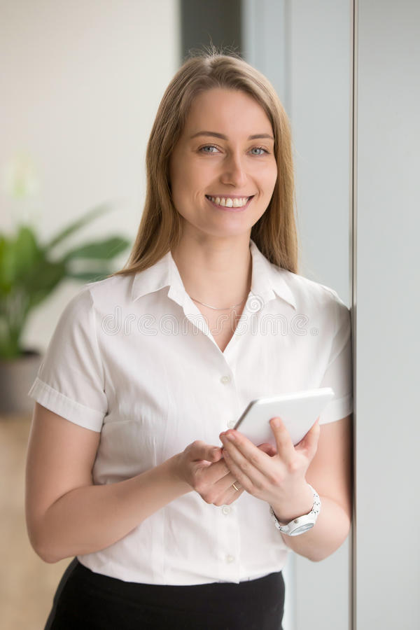 Smiling confident businesswoman holding digital tablet looking a. Smiling confident businesswoman holding digital tablet, looking at camera, enjoying using stock image