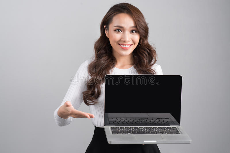 Smiling confident businesswoman showing laptop screen isolated o stock image