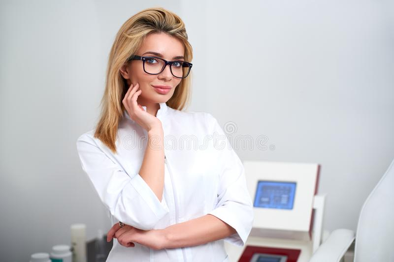 Smiling confident female beautician doctor in lab coat standing in her office with medical hardware and patient chair on stock images
