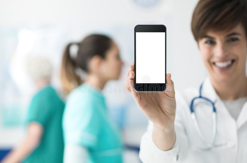 Female doctor holding a smartphone. Smiling confident female doctor holding a touch screen smartphone and medical staff on the background, medical app concept stock image