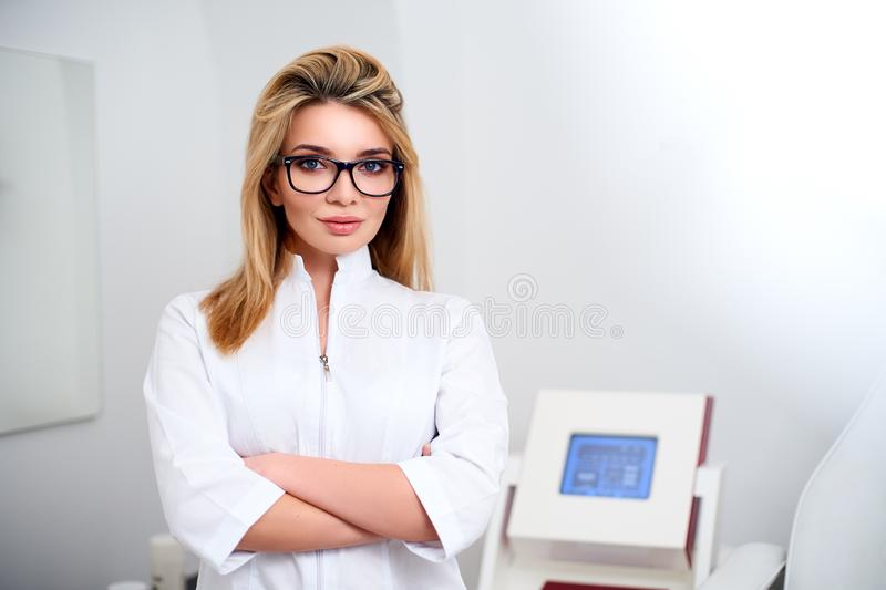 Smiling confident female doctor with lab coat on standing in her office with medical hardware and patient chair on royalty free stock photos