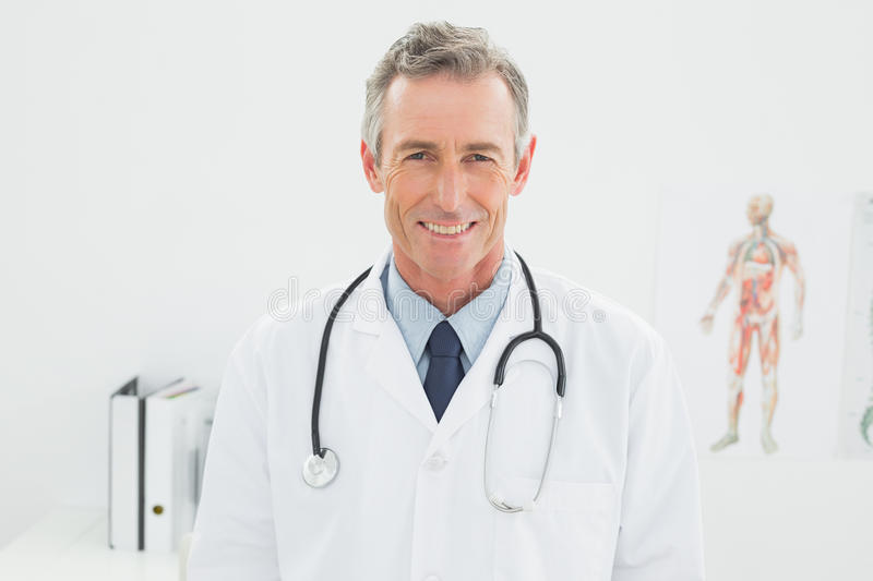 Smiling confident male doctor in medical office. Portrait of a smiling confident male doctor standing in the medical office royalty free stock photo