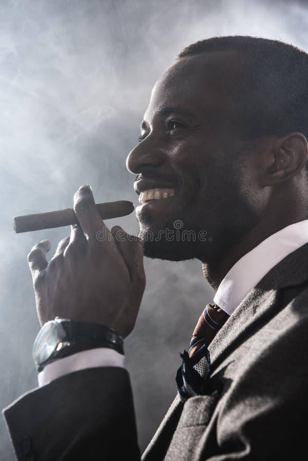 Smiling confident man smoking cigar indoors stock photography