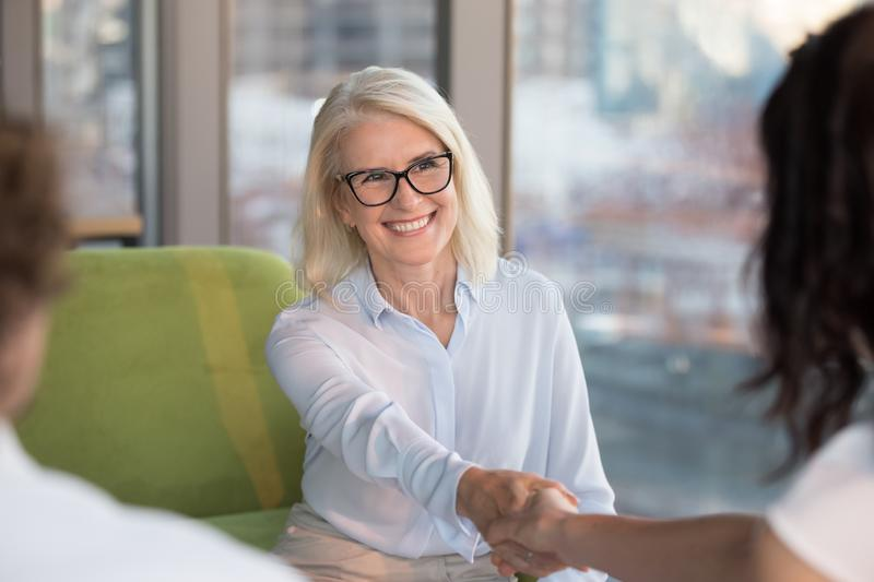 Smiling confident mature woman job seeker applicant handshaking hr. Smiling confident old mature women job seeker applicant handshaking hr making good first stock photos
