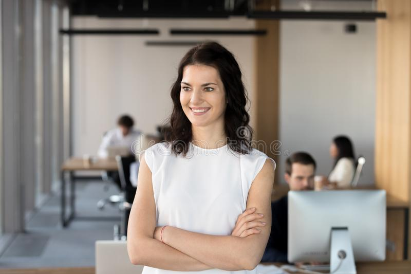 Smiling confident motivated female leader looking away dreaming of future. Achievements, young happy businesswoman corporate manager satisfied with successful stock image