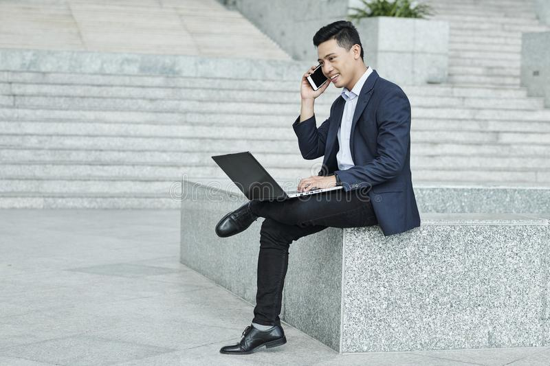 Entrepreneur calling coworker. Smiling confident Vietnamese entrepreneur sitting outdoor with laptop and calling coworker or employee stock images