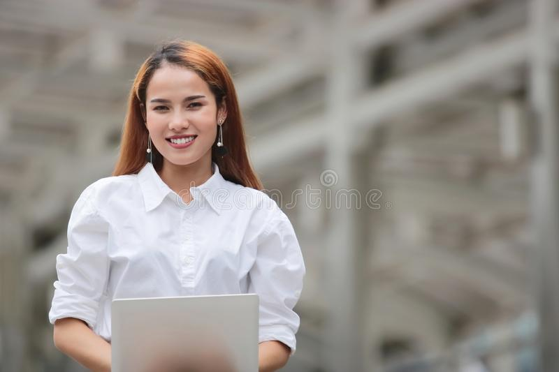 Smiling confident young Asian business woman using laptop for job at outside office royalty free stock photography