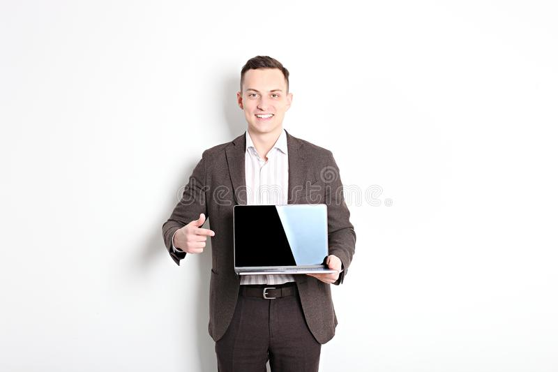Smiling confident young man, no tie, holding grey laptop device and typing while standing against solid white wall. Wireless inter royalty free stock images