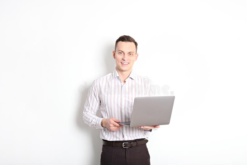 Smiling confident young man, no tie, holding grey laptop device and typing while standing against solid white wall. Wireless inter stock image