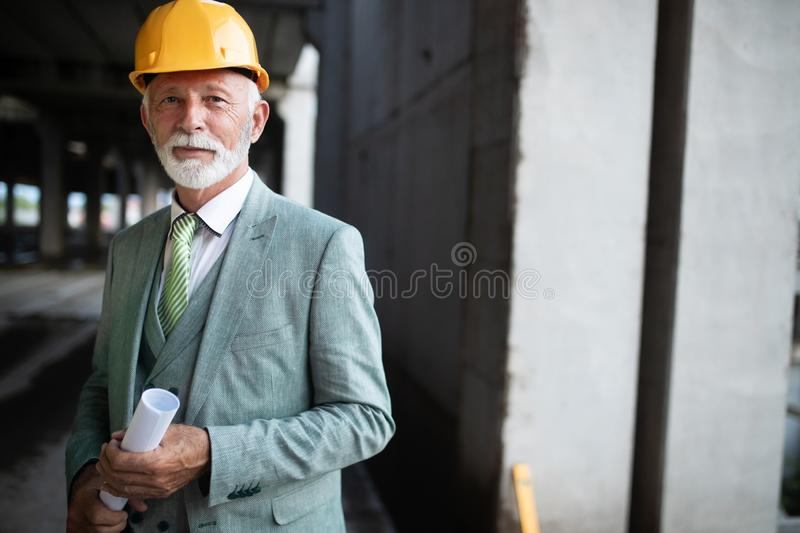 Smiling construction manager, engineer, businessman, architect standing on construction site royalty free stock photography