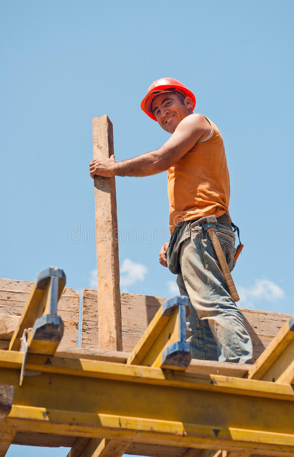 Smiling construction worker with formwork beam stock images
