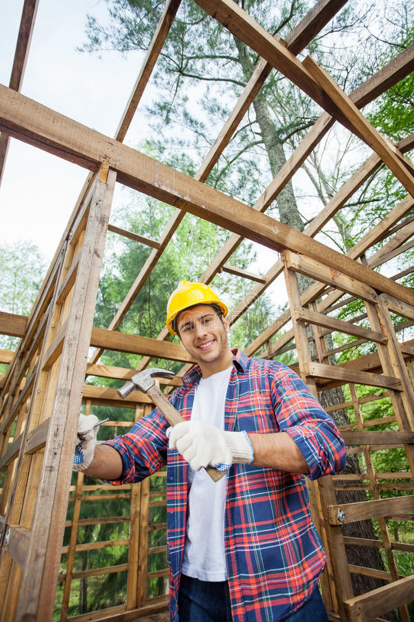 Smiling Construction Worker Hammering In Timber. Portrait of smiling construction worker hammering in incomplete timber cabin at site royalty free stock photo