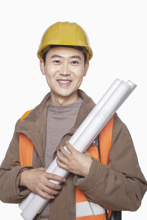 Smiling Construction worker holding blueprint against white background, portrait, looking at camera royalty free stock photography