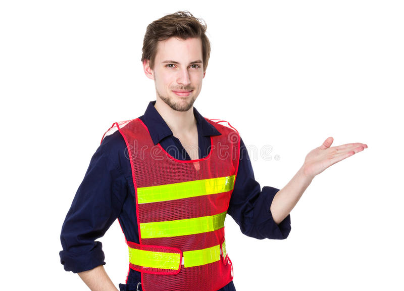 Smiling construction worker presenting product stock photo
