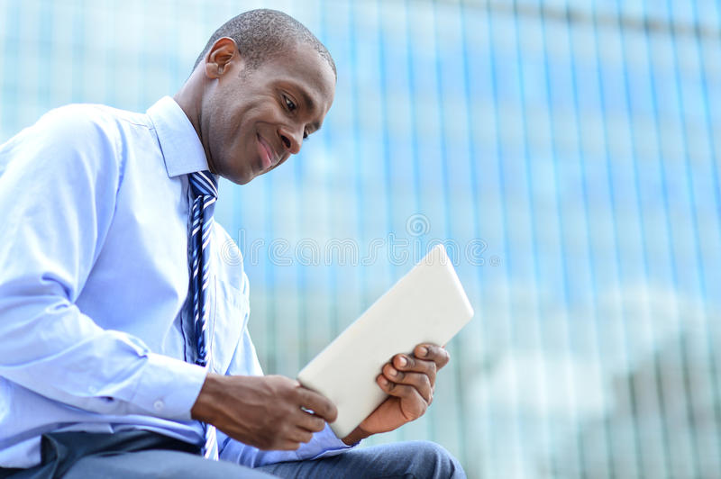 Smiling corporate executive using a tablet pc stock image