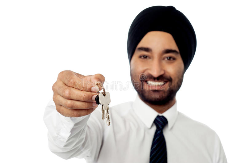 Smiling corporate guy holding a house key stock image