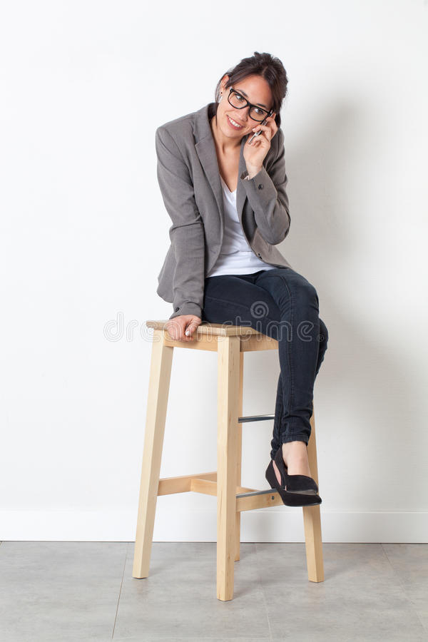 Free Smiling Corporate Woman Working With Cell Phone Sitting On Stool Stock Photos - 69966073