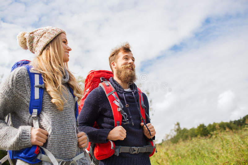 Smiling couple with backpacks hiking royalty free stock photo