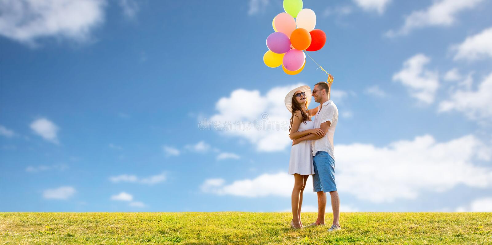 Smiling couple with balloons over sky and grass royalty free stock image