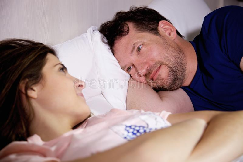 Happy couple looking each other in bed in love stock photos