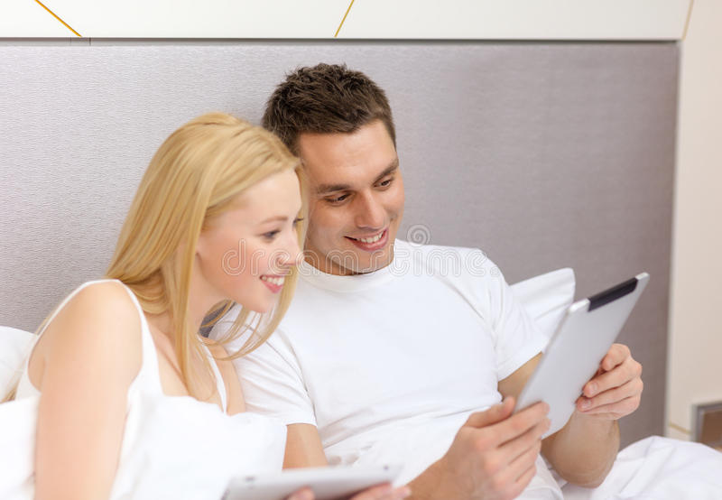 Smiling couple in bed with tablet pc computers. Hotel, travel, relationships, technology, intermet and happiness concept - smiling couple in bed with tablet royalty free stock images