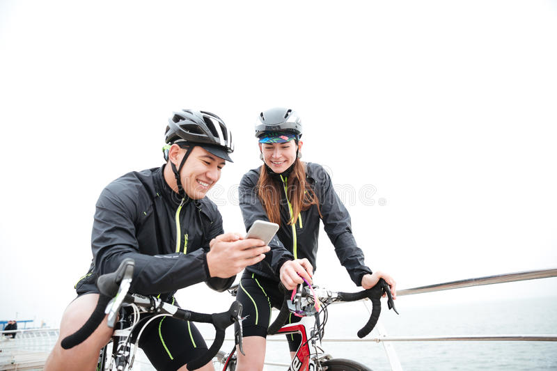 Smiling couple on bicycles resting and using smartphone royalty free stock images